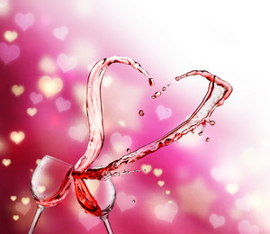 Heart splash from two glasses of red wine on abstract small heart lights background