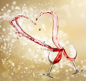 Heart splash from two glasses of red wine over golden light background
