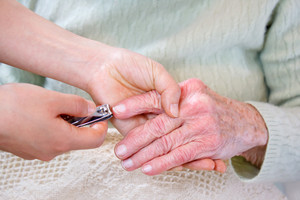 Helping senior woman cutting her fingernails
