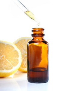 Herbal medicine dropper bottle with lemons on white background