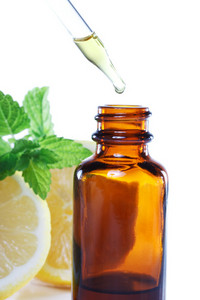 Herbal medicine dropper bottle with mint leaves and lemon