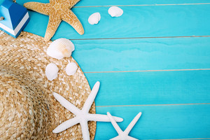 High Angle View of Beach Hat, Sea Shells and Starfish on Top of Light Cool Blue Table with Copy Space for Texts.