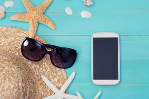 High Angle View of Mobile Gadgets with Starfish, Sea Shells and Beach Hat