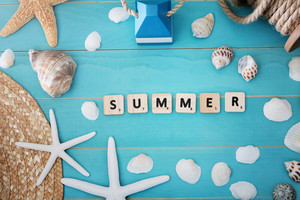 High Angle View of Wood Blocks on Light Blue Table with Assorted Sea Shells and Starfish for Summer Concept