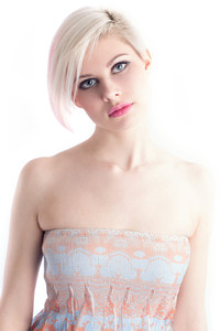 High key photo of a beautiful and glamorous young woman with creative hair style. Colored and natural retouched.