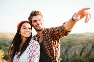 Hiking couple. Man showing the destination. Young happy couple on the hiking trail.