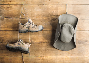 Hiking shoes and hat hang on a wooden fence background