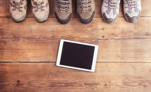 Hiking shoes and tablet laid on a wooden floor background