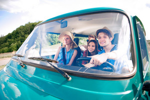 Hipster boy driving an old campervan with teenage friends, roadtrip, sunny summer day
