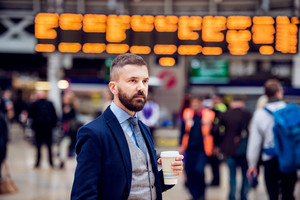 Hipster businessman holding a disposable coffee cup at the crowded train station