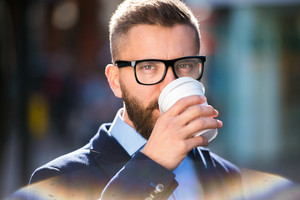 Hipster businessman holding a disposable cup and drinking coffee, walking in the street of London, wearing black eyeglasses