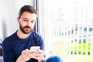 Hipster businessman in blue long sleeved t-shirt working from home, holding smart phone, texting