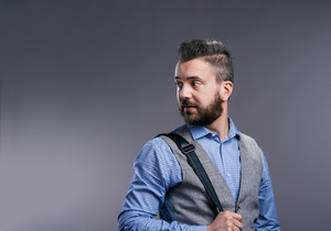Hipster businessman in blue shirt and gray vest, studio shot on gray background