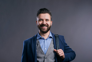 Hipster businessman in blue shirt and jacket, studio shot on gray background