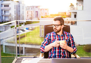 Hipster businessman in checked shirt sitting on a balcony, holding a cup of coffee, relaxing