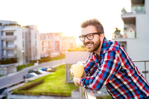 Hipster businessman in checked shirt standing on a balcony, holding a cup of coffee, relaxing