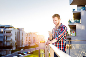 Hipster businessman in checked shirt with smart phone texting, standing on balcony