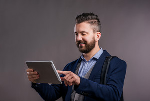 Hipster businessman in dard blue jacket with tablet, studio shot on gray background