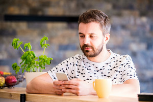 Hipster businessman in white t-shirt working from home, holding smart phone, texting