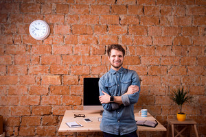 Hipster businessman sitting on office desk, smiling, against brick wall. Smart watch on hand and computer on the table. Coffee cup, personal organizer, smart phone and various office stuff around the workplace.