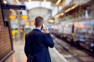 Hipster businessman with smartphone, making a phone call, waiting at the train station platform, back view, rear, viewpoint