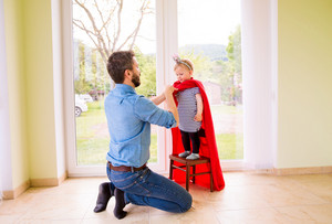 Hipster father with his cute little princess daughter in red super hero cape, dressing her