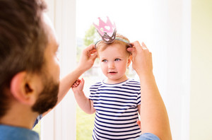 Hipster father with his daughter in striped t-shirt putting hairband with crown on her head