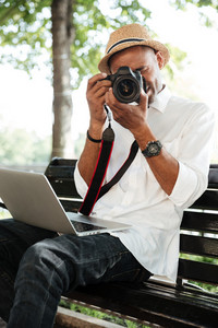 Hipster makes photo in park. with laptop