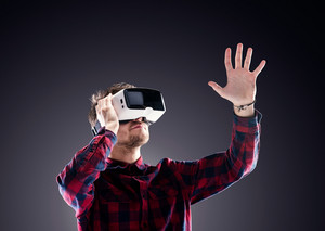 Hipster man in checked shirt wearing virtual reality goggles, reaching out. Studio shot on black background