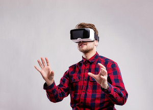 Hipster man in checked shirt wearing virtual reality goggles. Studio shot on gray background