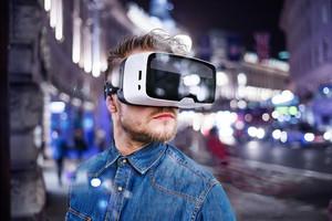 Hipster man in denim shirt wearing virtual reality goggles. City at night. London, England.