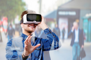 Hipster man in denim shirt wearing virtual reality goggles. Crowded street of London.