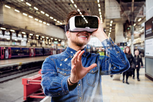 Hipster man in denim shirt wearing virtual reality goggles, standing at train station.