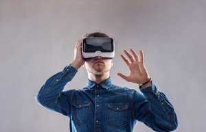 Hipster man in denim shirt wearing virtual reality goggles stretching arms. Studio shot on gray background