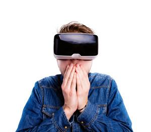 Hipster man in denim shirt wearing virtual reality goggles. Studio shot on white background