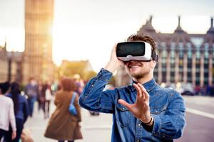 Hipster man in denim shirt wearing virtual reality goggles. Westminster bridge. Big Ben, London, England.