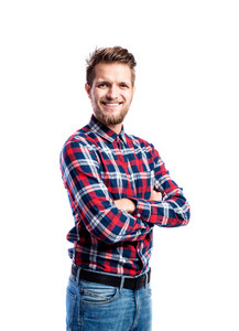 Hipster man in jeans and checked shirt, arms crossed, studio shot on white background, isolated