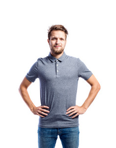 Hipster man in jeans and gray t-shirt, arms on hips, studio shot on white background, isolated