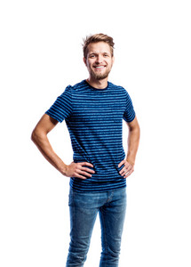 Hipster man in jeans and striped blue t-shirt, arms on hips, studio shot on white background, isolated