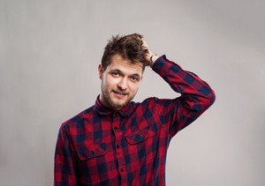 Hipster man in red checked shirt smiling, scratching head. Studio shot on gray background
