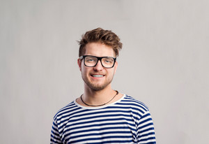 Hipster man in striped black and white long sleeve t-shirt and eyeglasses. Studio shot on gray background