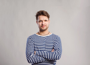 Hipster man in striped black and white long sleeve t-shirt. Studio shot on gray background