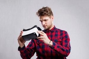 Hipster man in striped black and white sweatshirt holding virtual reality goggles. Studio shot on gray background