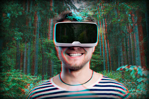 Hipster man in striped black and white sweatshirt wearing virtual reality goggles. Green forest.