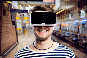 Hipster man in striped black and white sweatshirt wearing virtual reality goggles, standing at train station.