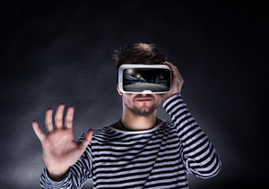 Hipster man in striped black and white sweatshirt wearing virtual reality goggles. Studio shot on black background