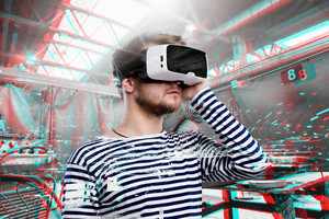 Hipster man in striped black and white sweatshirt wearing virtual reality goggles. Welding factory.