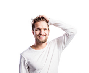 Hipster man in white long-sleeved t-shirt, holding hair, studio shot on white background, isolated