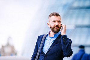 Hipster manager holding a smart phone, making a phone call, City Hall, London