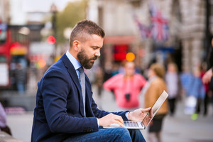 Hipster manager sitting on stairs on sunny Piccadilly Circus, London, working on laptop